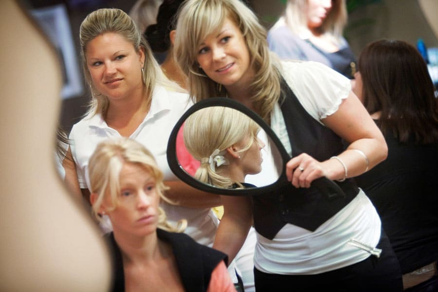 Bride, bridesmaid and hair stylist scrutinizing brides hair.