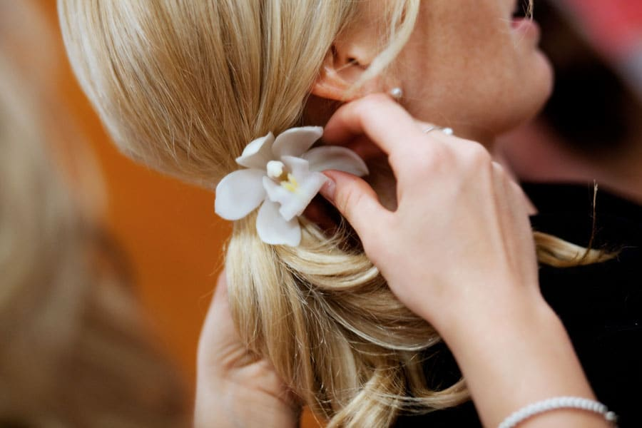 Closeup of bride's hair with flower being placed in pony tail
