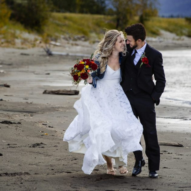 couple walking and laughing as they walk along Jasper Lake beach- unique wedding photography