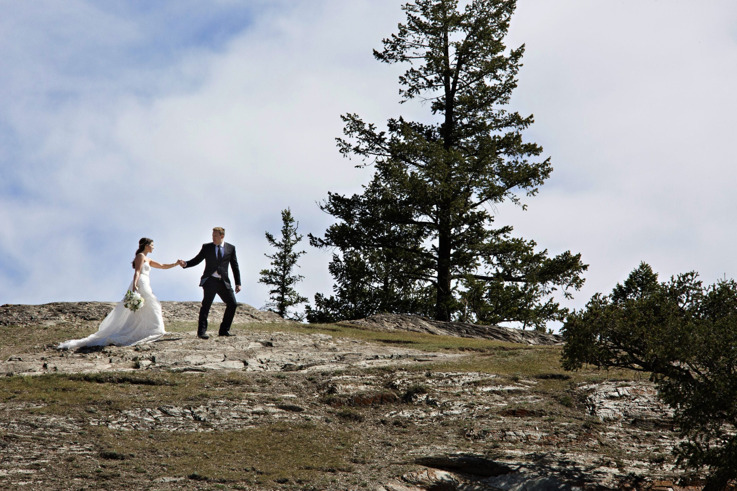 wedding couple walking on top of old fort point in Jasper