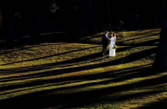 couple standing in mottled light jasper park lodge