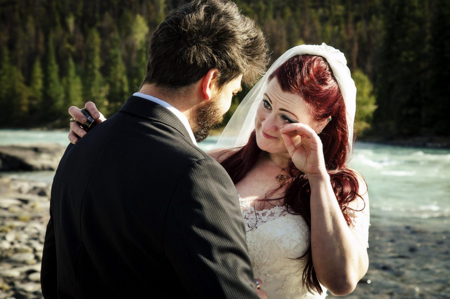 bride and groom exchanging a tender moment by athabasca river