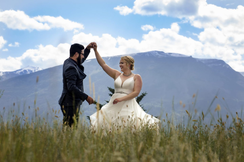 Bride and groom dancing in a meadow