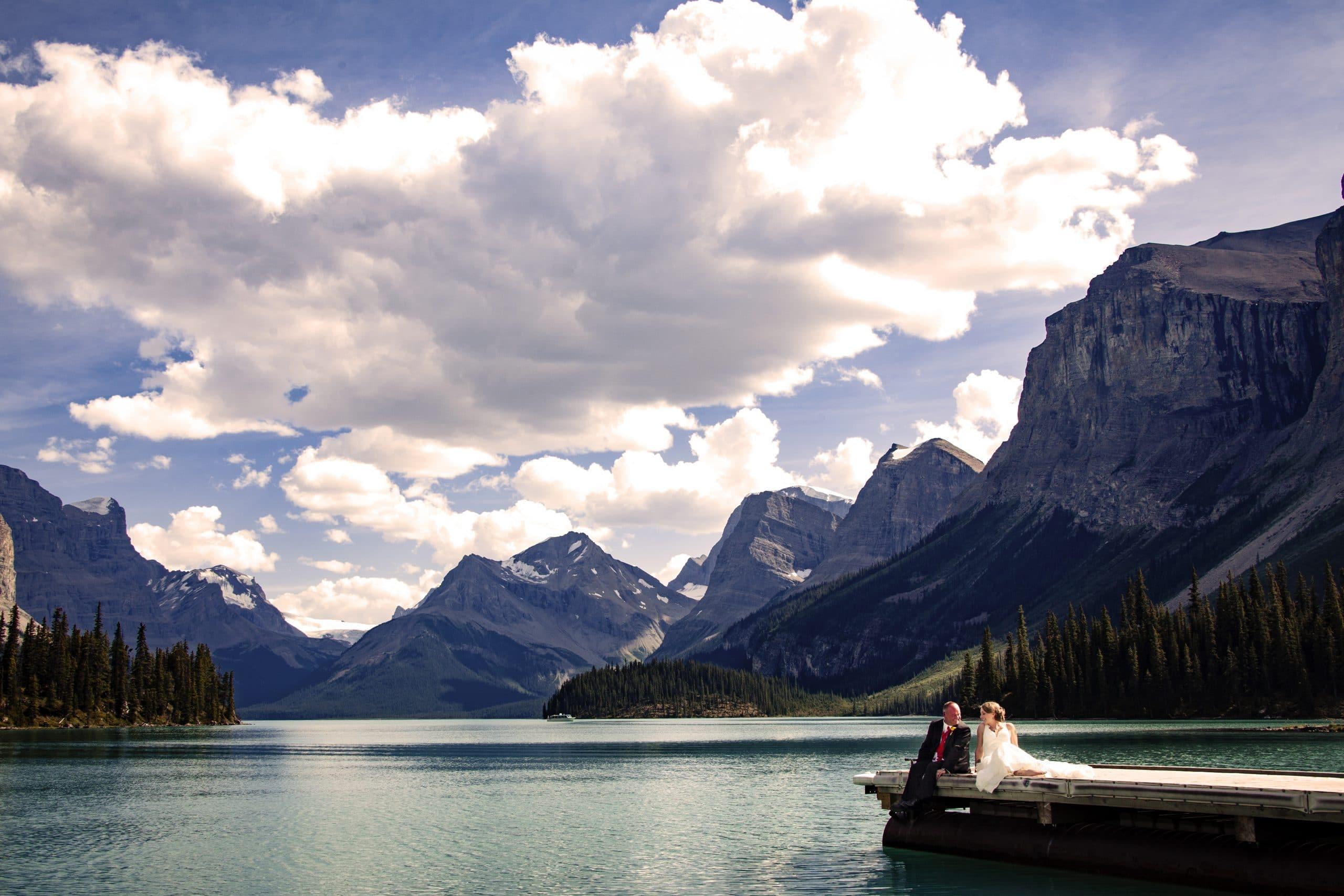 wedding couple sitting on a dock at Maligne Lake - Your Jasper wedding photography consultation