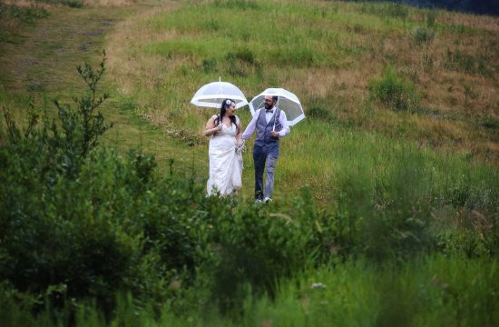wedding couple walking in the rain with umbrellas get great wedding photos even in the rain
