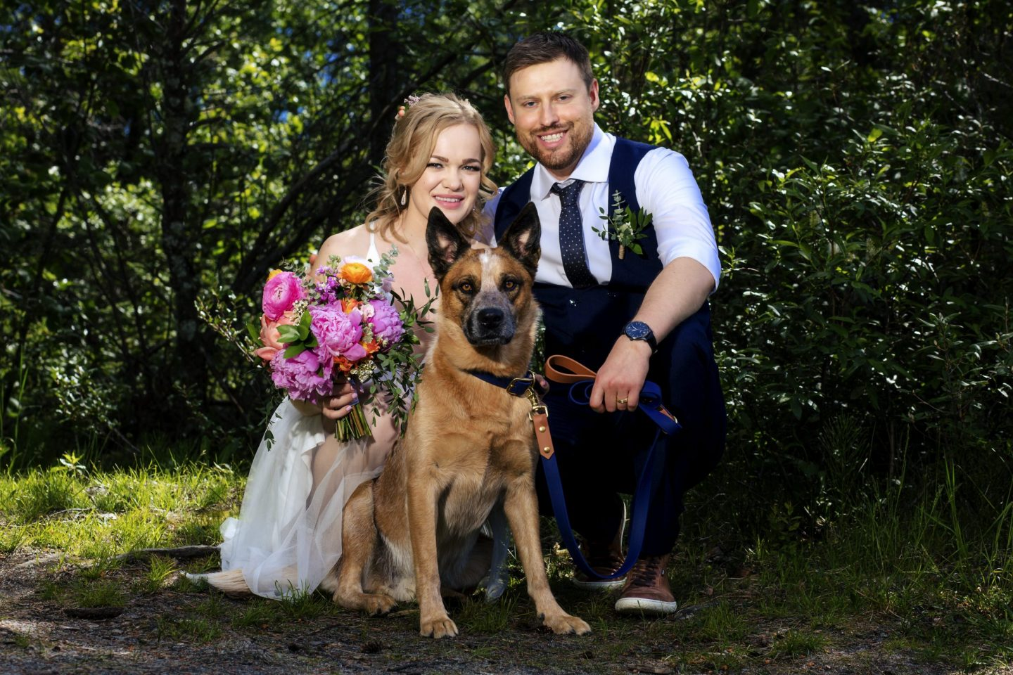 wedding couple crouching down and posing with dog in the centre- getting married in Jasper