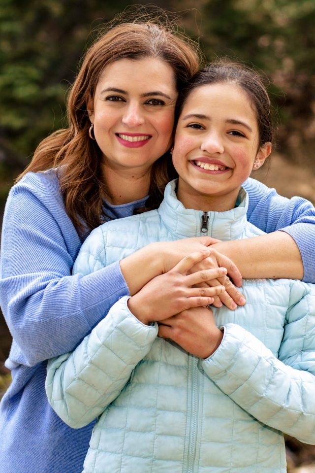 mother wrapping her arms around daughter- family photography
