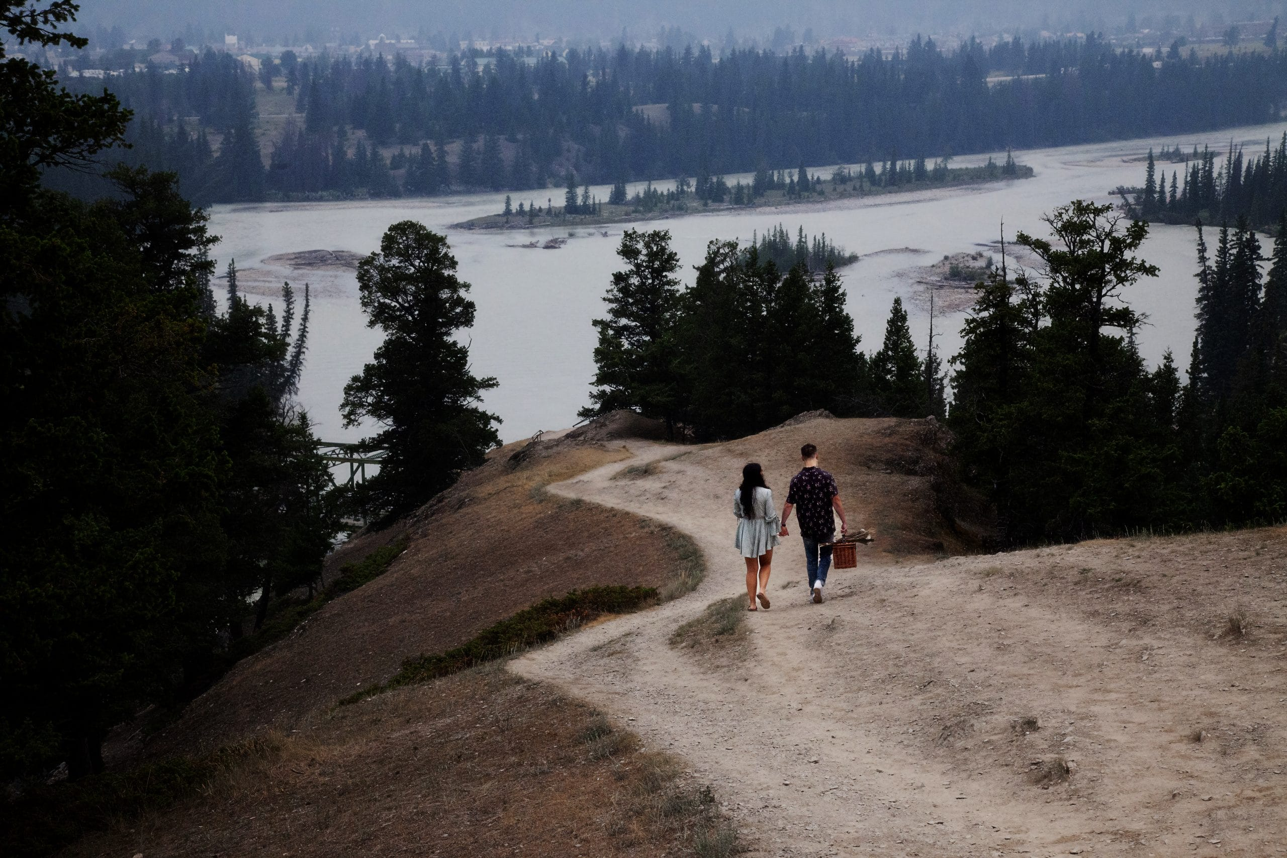 man and woman descending hill from behind at Old Fort Point Jasper -enagement photography Jasper