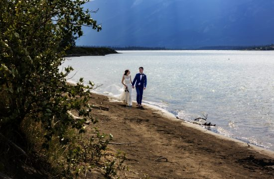 Wedding couple walking along Jasper Lake