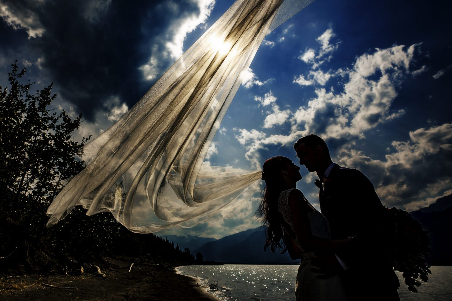 Silhouette of wedding couple against clouds and blue sky- Jasper Lake Wedding Photos